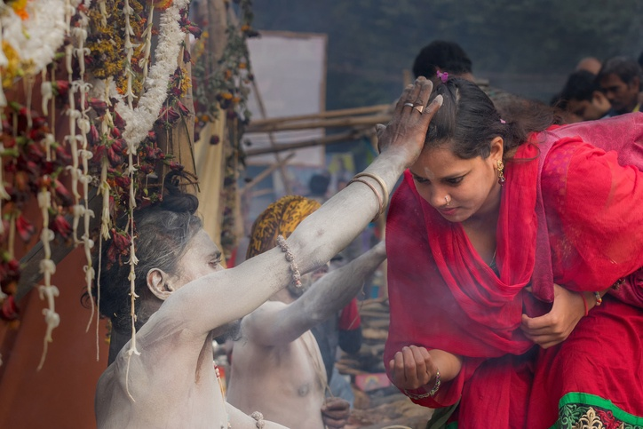 A Hindu Sadhu with white ash applied on the body and the face, blesses an Indian devotee woman